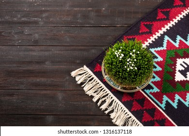 Novruz Green wheat grass semeni or sabzi, Azerbaijan, Persian new year on oriental motives pattern rug on wooden dark brown background. National folk carpet with white tassels, copy space