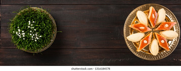 Novruz Green wheat grass semeni or sabzi, samani,Azerbaijan, Persian new year with traditional national pastry pakhlava and shekerbura in golden tray on wooden dark brown background. copy space banner