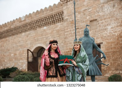 Novruz holiday in Azerbaijan. Two women in national clothes holding sprouts of spring wheat grass semeni for Novruz holiday