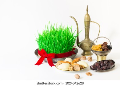 Novruz national Azerbaijan holiday spring new year celebration concept, wheat grass semeni, pear shape glass of tea, traditional pakhlava shekerbura, dry fruits, kelagai, vintage jar white background