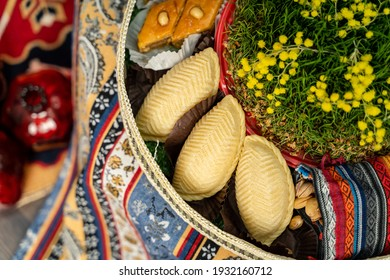 Novruz plate with Azerbaijan national pastry shekerbura and green semeni wheat grass with glass pomegranate and nuts
