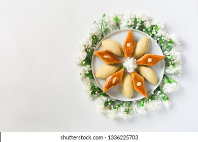 Novruz plate of traditional Azerbaijan pastry pakhlava and shakarbura, beautiful white flowers for spring equinox celebration on white background, flat lay top view copy space for text for nowruz