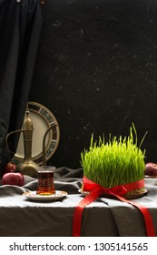 Novruz setting in Azerbaijan with black tea in armudu pear shape drinking glass with green wheat grass semeni with red ribbon for celebration. Spring equinox, persian nowruz greeting card copy space