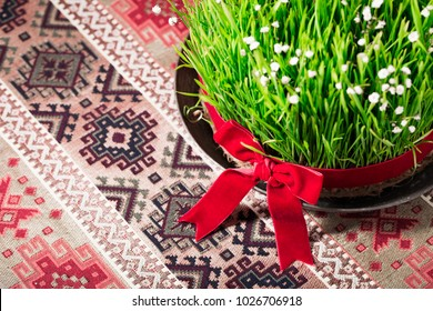 Novruz setting table decoration, semeni fresh wheat grass decorated with red ribbon bow on ethnic motives rustic table cloth, new year sring celebration, nature awakening concept, copy space for text