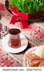 Novruz setting table decoration, tea in  tulip shape glass on ethnic motives rustic table cloth with wheat grass, dyed eggs, traditional sweets, samovar, new year sring celebration, nature awakening