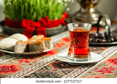 Novruz setting table decoration, tea in  tulip shape glass on ethnic motives rustic table cloth with wheat grass, dyed eggs, traditional sweets, samovar, new year spring celebration, nature awakening