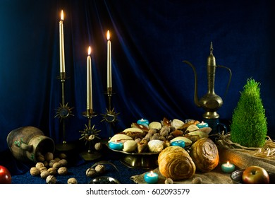 Novruz still life with candles, copper tray with traditional national pastry, and clay jar