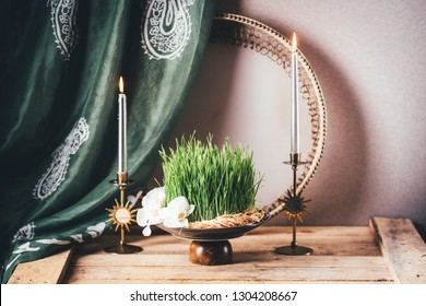 Novruz still life with semeni sabzi wheatgrass , silk national scarf, eastern musical instrument and golden candles. Spring equinox in March celebration, copy space