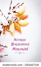"Novruz traditional Azerbaijan pastry shekerbura and pakhlava with beautiful tiny apricot or cherry blossoms. Translation: ""Happy Nowruz!"" spring equinox greeting card on pink background, copy space"