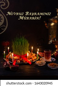 """Novruz traditional tray with green wheat grass semeni or sabzi, sweets and dry fruits and festive candles with tea and samovar. Translation: """"Happy Nowruz"""" greeting card, copy space"""