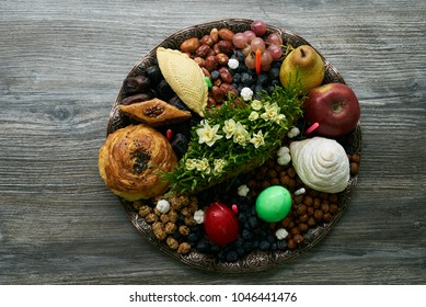 Novruz tray with Azerbaijan national pastry pakhlava,  shekerbura, gogal, badambura and dry snacks with green semeni wheat grass on rustic wooden table background