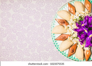 Novruz tray plate with Azerbaijan national pastry pakhlava and shekerbura, light grey background with buta paisley motives daffodils purple fleur de lis flowers spring new year celebration copy space