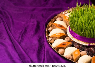 Novruz tray plate with Azerbaijan national pastry pakhlava and shekerbura purple silk scarf background with dry fruits, fresh green semeni wheat grass eastern spring new year celebration copy space