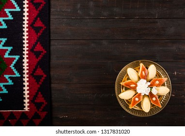 Novruz tray with shekerbura and pakhlava, Azerbaijan traditional pastry for spring equinox and Persian Nowruz, Navruz new year celebration on dark brown wooden background with rug carpet