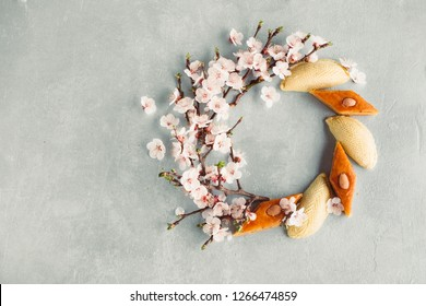 Novruz wreath made of traditional Azerbaijan pastry shekerbura and pakhlava, beautiful tiny blossoms for spring equinox celebration on grey background, flat lay top view copy space for text for nowruz