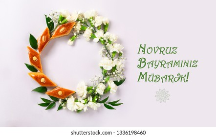 Novruz wreath made of traditional Azerbaijan pastry pakhlava, beautiful white for spring equinox celebration on light lilac background, flat lay top view copy space for text for nowruz