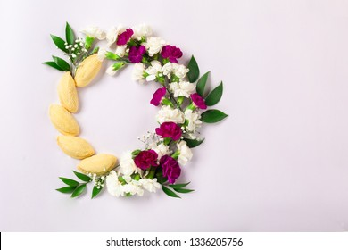 "Novruz wreath made of traditional Azerbaijan pastry shekerbura and beautiful white, violet flowers for spring celebration, light lilac background, top view. Translation: ""Happy Nowruz"" greeting card"