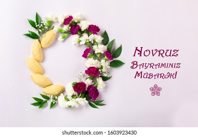 """Novruz wreath made of traditional Azerbaijan pastry shekerbura and beautiful white, violet flowers for spring celebration, light lilac background, top view. Translation: """"Happy Nowruz"""" greeting card"""