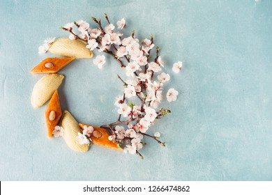 Novruz wreath mock up made of traditional Azerbaijan pastry shekerbura and pakhlava, beautiful tiny blossoms for spring equinox celebration on blue background, flat lay top view copy space for text