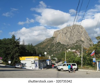 NOVYY SVET, RUSSIA - SEPTEMBER 25, 2014: Township square, minimarket pavilion, transport stop, people at minibus, mountain Sokol above, blue clody sky on back plane