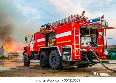 NOVYY URENGOY, RUSSIA - AUGUST 3, 2015: Red firetruck Ural 5557 takes part in the extinguishing of a fire in an old wooden house.