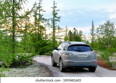 Novyy Urengoy, Russia - June 26, 2017: Motor car Infiniti FX35 in the forest at the background of the sunset.