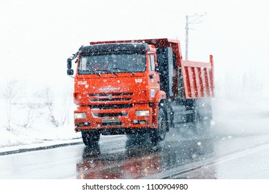 Novyy Urengoy, Russia - May 29, 2018: Orange dump truck KAMAZ 6520 with CNG fuel engine in the city street during a heavy blizzard.