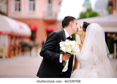 Now groom may kiss the bride, wedding couple kissing at street