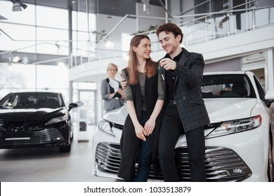 Now her dream comes true. Car salesman giving the key of the new car to the young attractive owners.