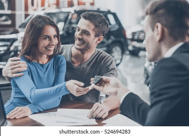 Now her dream comes true. Car salesman giving the key of the new car to the young attractive owners