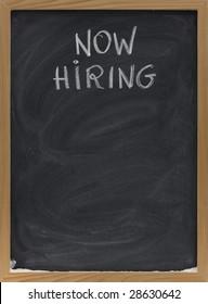 now hiring advertisement handwritten with white chalk on blackboard, copy space below, eraser smudges