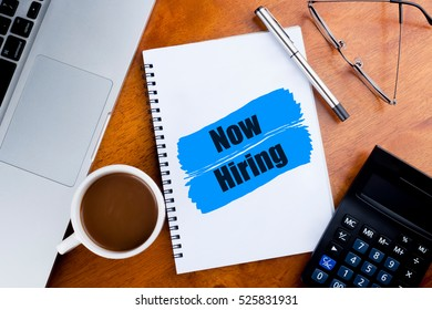 """Now Hiring"" words on notebook with a cup of coffee, pen, calculator, spectacles, and a a laptop -  jobs and business concept"