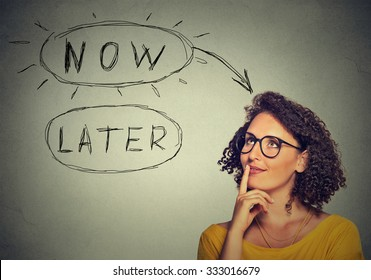 Now or later. Woman thinking looking up isolated on grey wall background. Human face expression