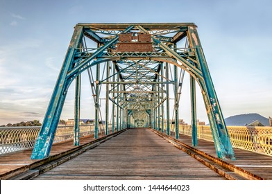 Now a pedestrian crossing, the Walnut Street Bridge, built in 1890, spans the Tennessee River in Chattanooga with historic Lookout Mountain in the background early in the morning.