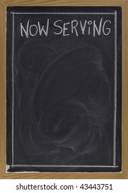 now serving - white chalk handwriting on blackboard with blank space below for a menu