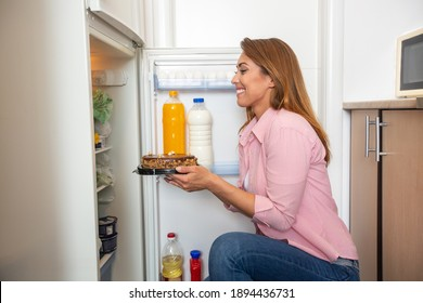 And now you are mine. Young woman taking the sweet tasty donuts from the refrigerator ready to eat them all