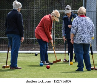 Nowra, NSW / Australia - 09/26/2019: Four mature females enjoy playing the outdoor game of croquet on lawn. Croquet a strategy sport,  person  hits plastic balls with a mallet through a hoop.