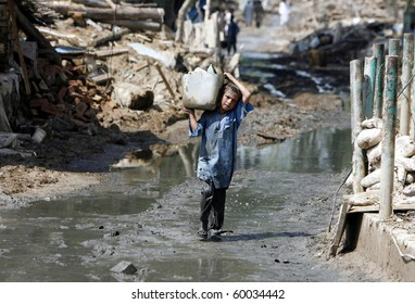 NOWSHERA, PAKISTAN - AUG 29: A child carries household items while passing through the rubble of houses on August 29, 2010 in Nowshera. The homes were destroyed by flood waters.