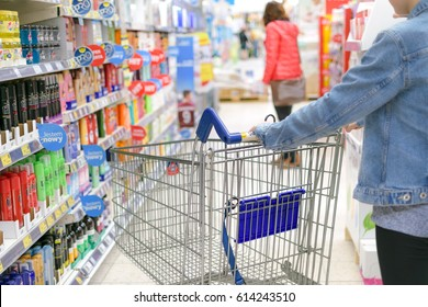 Nowy Sacz, Poland - March 29, 2017: Young woman pushing shopping cart through front of aisle with a variety of personal care products in a Tesco Hypermarket.