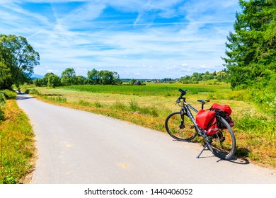 NOWY TARG, POLAND - JUN 29, 2019: Touring bike on cycling way in green farming fields along Dunajec river, Pieniny Mountains, Poland.