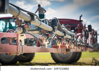 nozzles on the spray bar, against the background of the sprayer and the person standing on the barrel, during refueling