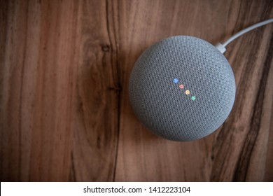 NRW/GERMANY - MAY 31, 2019: A Google Home Mini device on a wooden table.