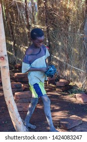 Nsanje/Malawi - 04 20 2019: barefoot thin Malawian boy wearing shorts carries a crude football made out of plastic bags