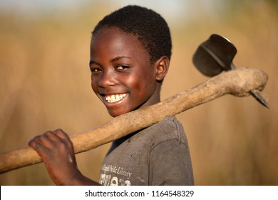 NTCHISI, MALAWI - JUNE 21, 2018: Unidentified happy boy with a hoe in a field in a remote village near Ntchisi. Malawi is one of the poorest countries in the world.