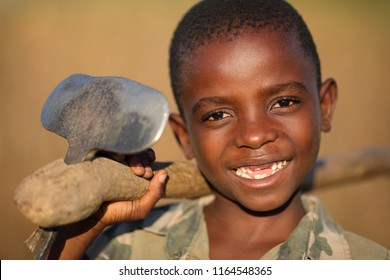 NTCHISI, MALAWI - JUNE 21, 2018: Unidentified happy boy with a hoe in a remote village near Ntchisi. Malawi is one of the poorest countries in the world.