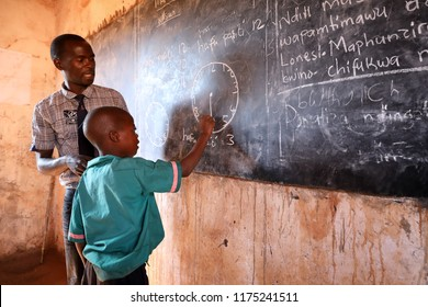 NTCHISI, MALAWI - JUNE 29, 2018: Unidentified student and teacher in a classroom of a primary school in a remote village near Ntchisi. Malawi is one of the poorest countries in the world.