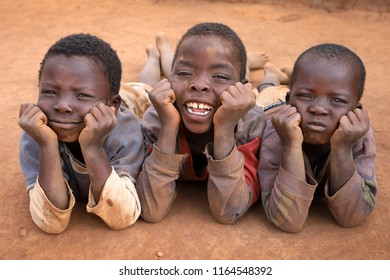 NTCHISI, MALAWI - JUNE 30, 2018: Unidentified boys relax on the ground in a remote village near Ntchisi. Malawi is one of the poorest countries in the world.