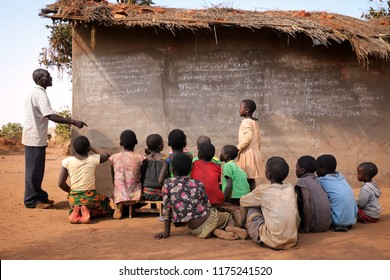 NTCHISI, MALAWI - JUNE 30, 2018: Unidentified students study in front of a small school building in a remote village near Ntchisi. Malawi is one of the poorest countries in the world.