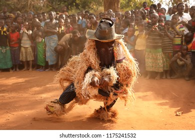NTCHISI, MALAWI - JUNE 30, 2018: Unidentified traditional Nyau dancers with face masks at a Gule Wamkulu ceremony in a remote village near Ntchisi. Malawi is one of the poorest countries in the world
