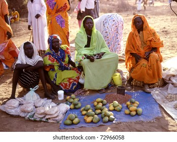NUBA MOUNTAINS,SUDAN - SEPTEMBER 7: women in the market selling papayas on  September 7, 2008 in the Nuba Mountains, Sudan. A small market in the Nuba Mountains run by women